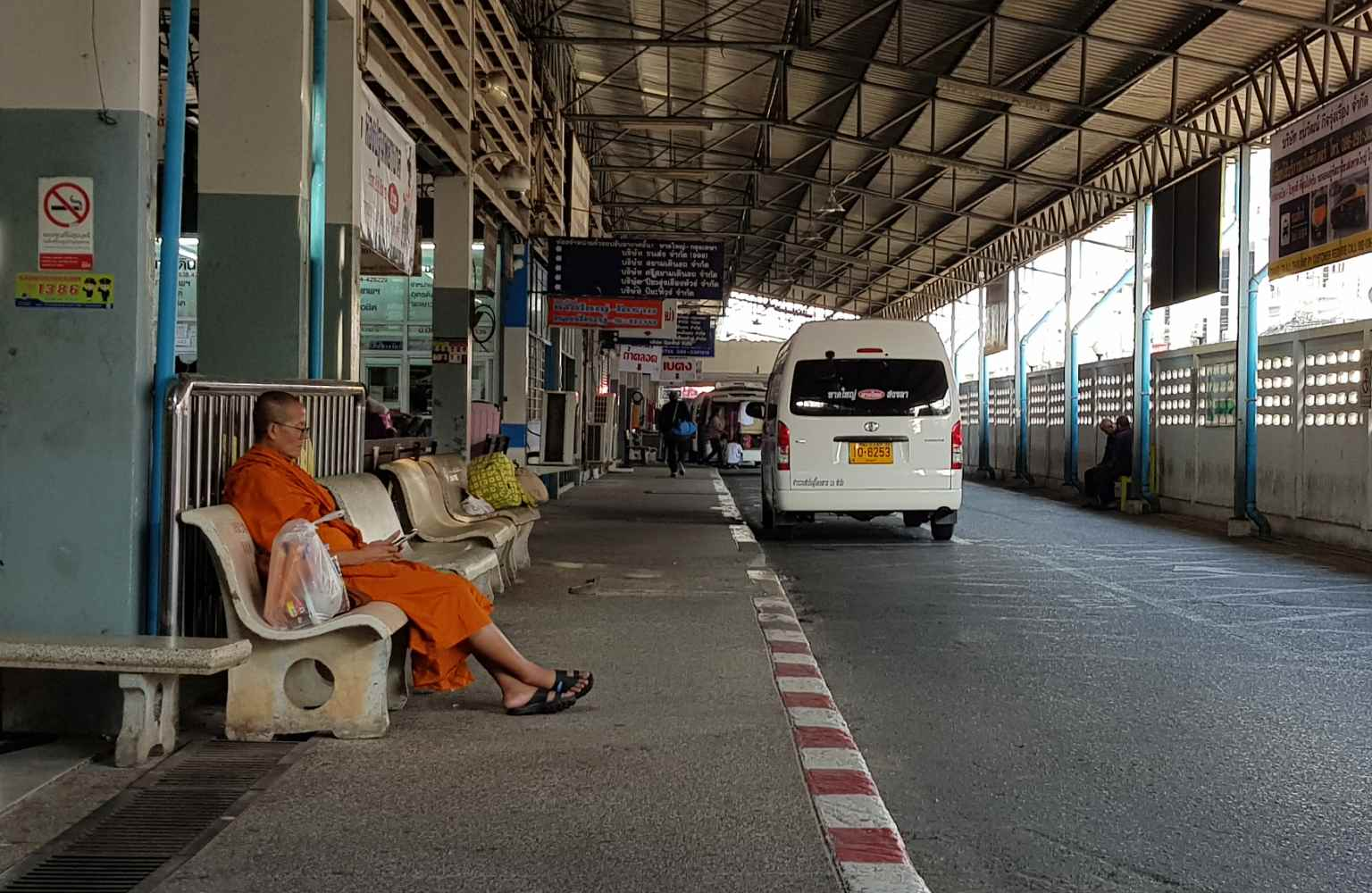 Buddhist monk waiting at the bus station of Hat Yai