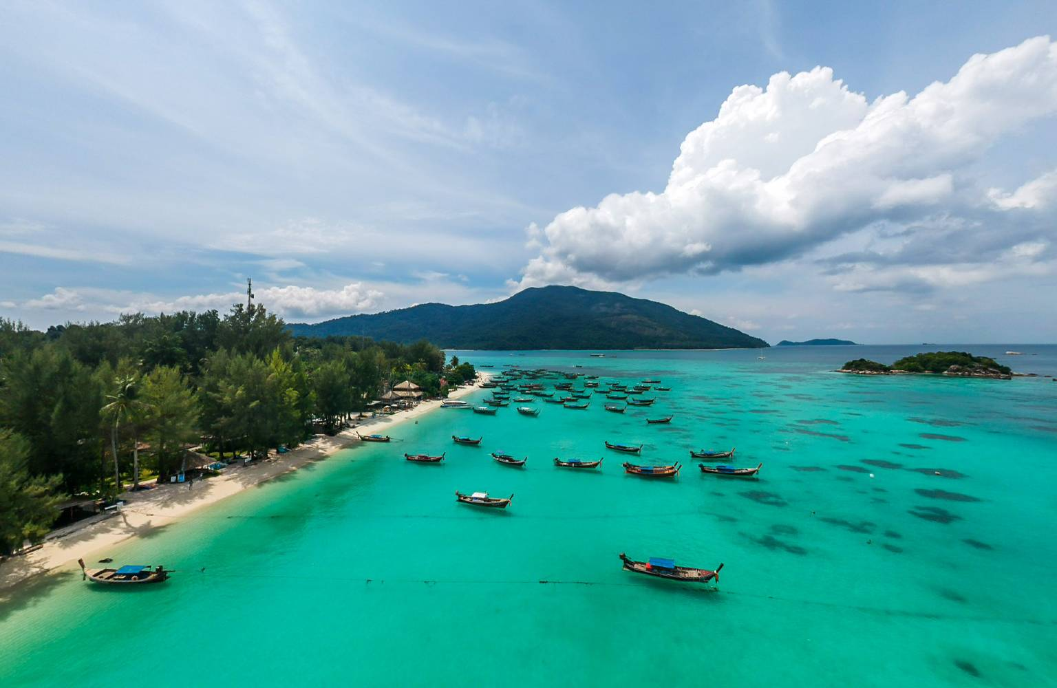 The coast of Koh Lipe with beautiful blue-green water and many longtail boats