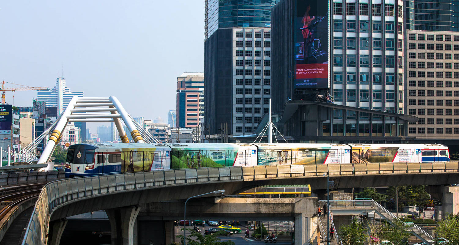 BTS Sky Train in the center of Bangkok above the traffic on the road.