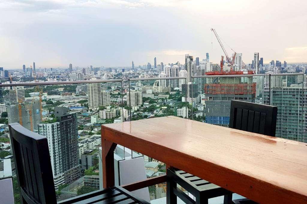 Aan een bartafel zitten terwijl je geniet van het uitzocht op de skyline van Bangkok bij Octave Sky Bar