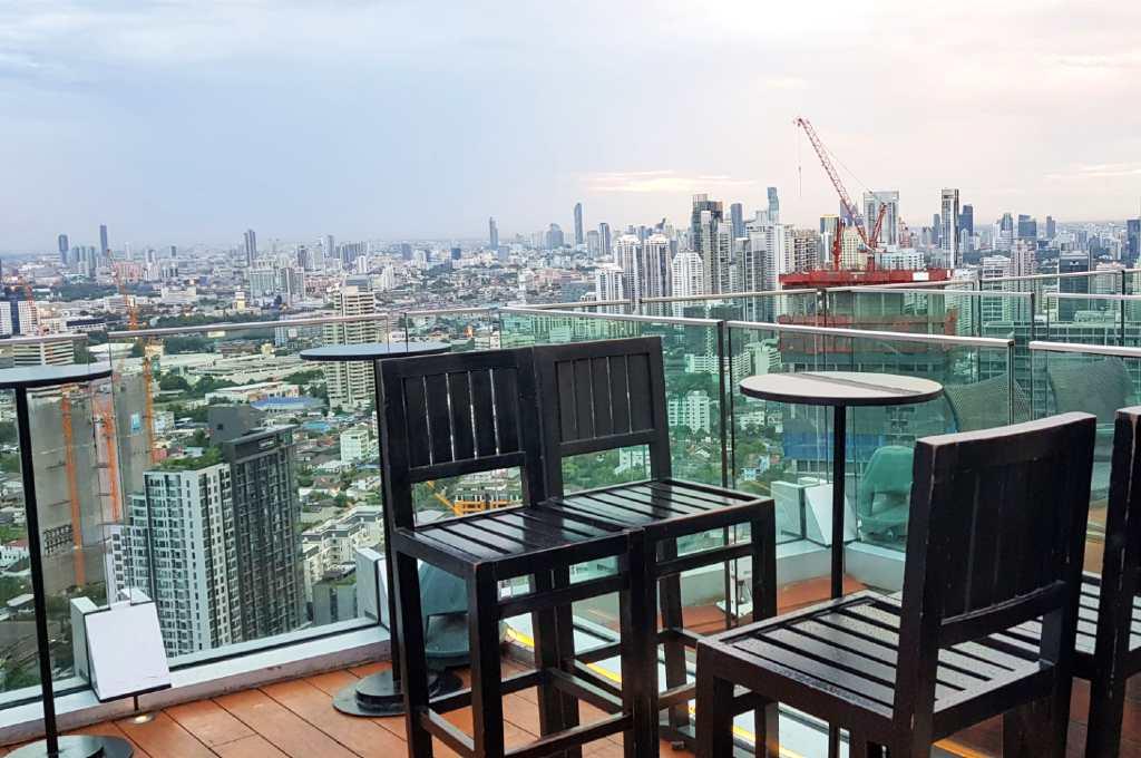 Zitten aan een tafeltje met barkrukken en genieten van het uitzicht van de skyline van Bangkok vanaf Octave Sky Bar
