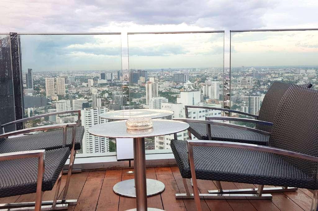 Lounge stoelen met uitzicht over de skyline van Bangkok vanaf Octave Rooftop Lounge & Bar
