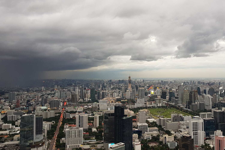 Hevige regenbui gezien vanaf The Peak op het King Power Mahanakhon gebouw in Bangkok