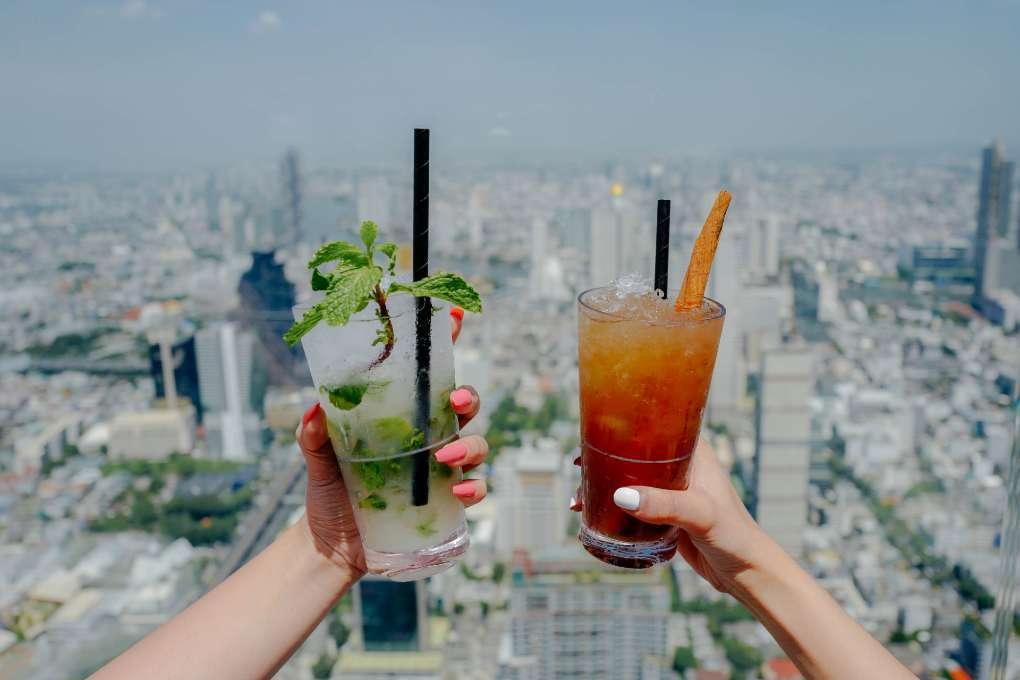 Proosten met cocktails op het Mahanakhon gebouw in Bangkok met een uitzicht over de skyline van Bangkok