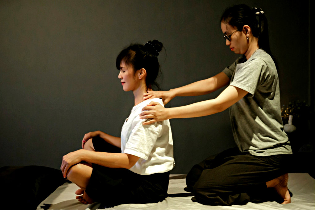 A blind masseur wearing sunglasses massages the shoulders of a woman sitting in a tailor's seat.