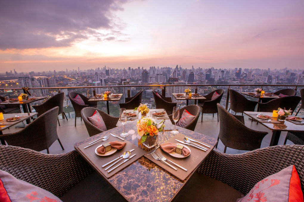Dining at Cielo Sky Bar & Restaurant in Bangkok, Thailand. You can see tables and chairs and the beautiful view from Cielo.