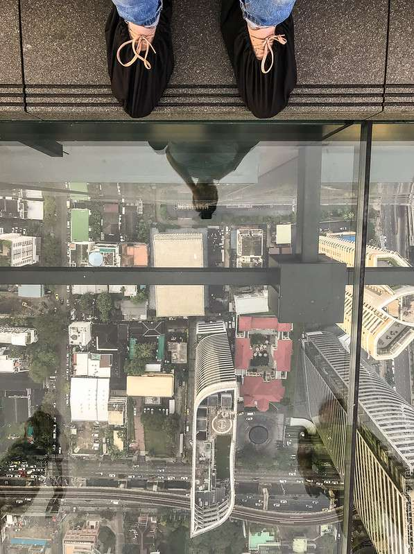 Eerste stap op het glazen platform van de Mahanakhon SkyWalk in Bangkok