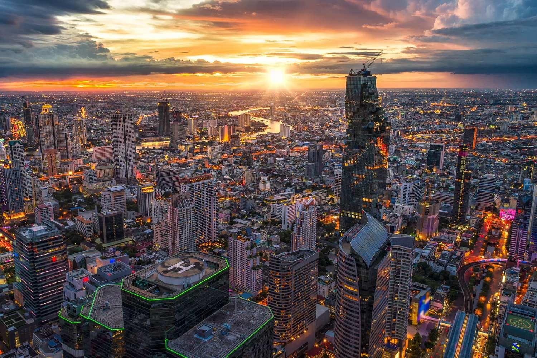 Zonsondergang met uitzicht over de skyline van Bangkok en het King Power Mahanakhon gebouw