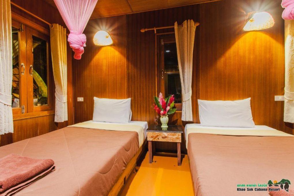 Een slaapkamer met twee losse eenpersoonsbedden in het Khao Sok Cabana Resort