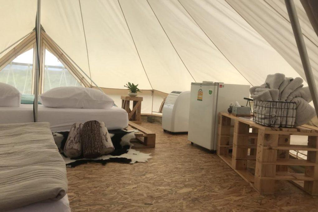 Binnenin de tent van Tanoshi Glamping is er een koelkast.mobiele airco een eenpersoonsbed en tweepersoonsbed