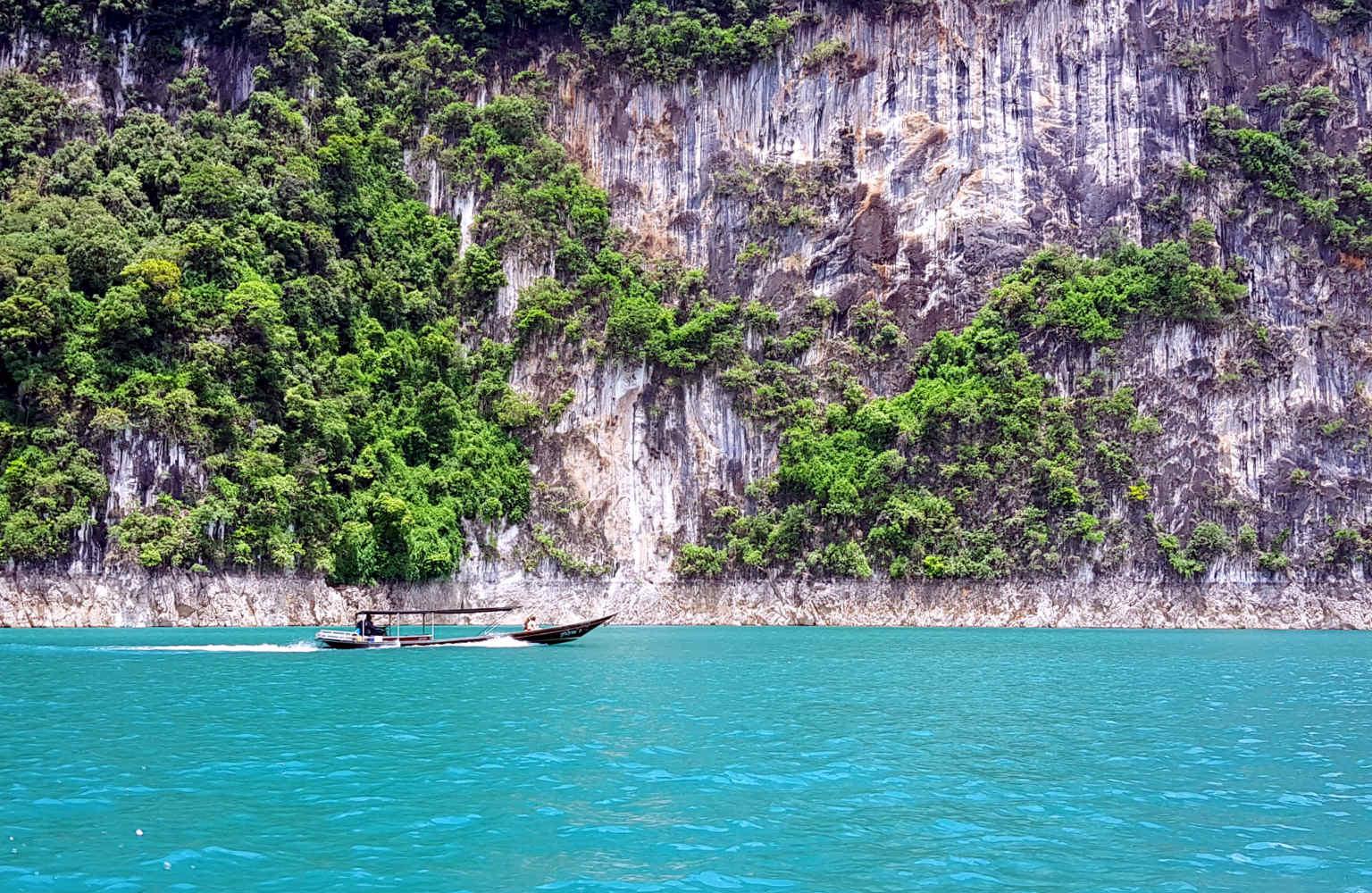 Cheow Lan Lake longtailboot in blauw water en kalksteen kliffen