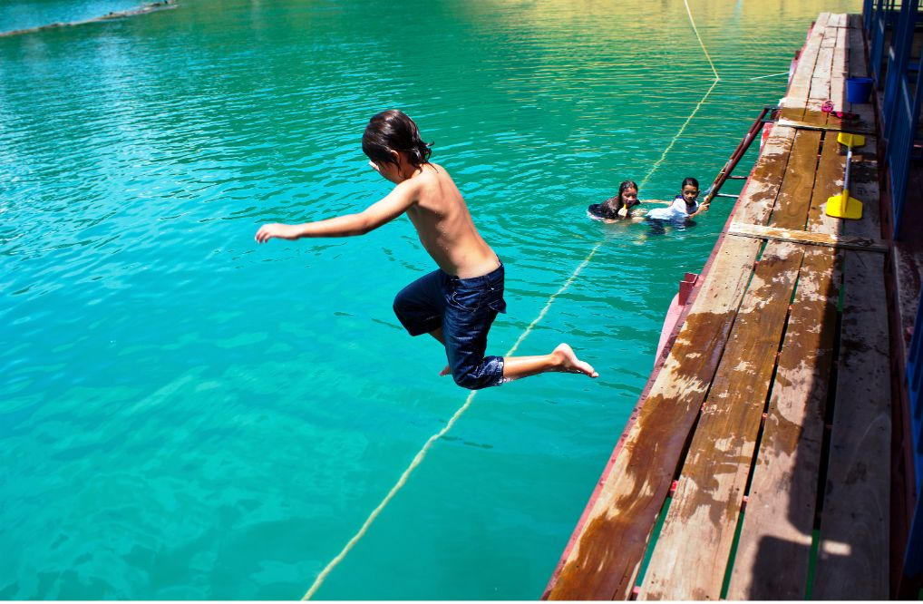 Cheow Lang Lake, child jumping in the blue water of the lake.