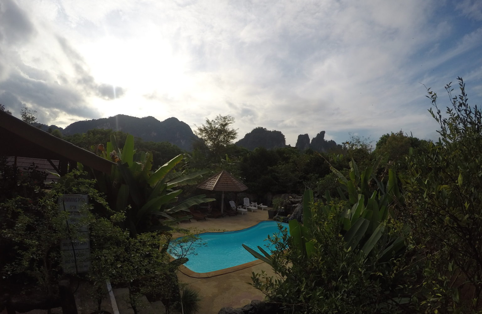 The pool at the Khao San Morning Mist Resort with surrounding tropical garden and distant limestone rock formations