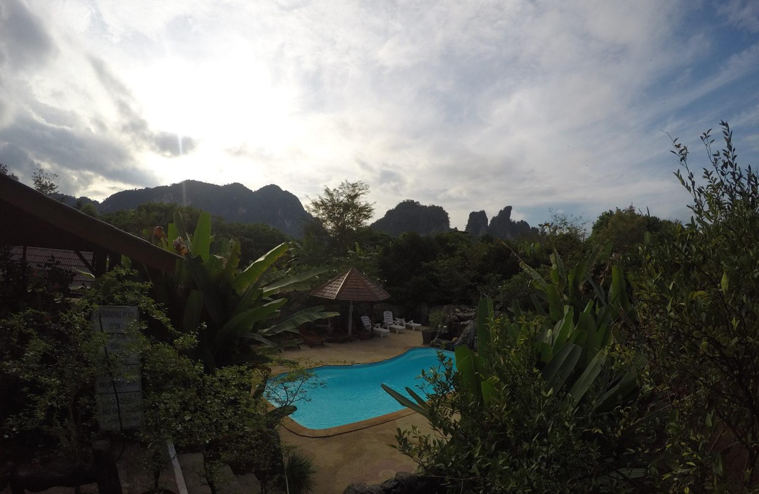 Het zwembad van het Khao San Morning Mist Resort met omliggende tropische tuin en in de verte kalkstenen rotsformaties