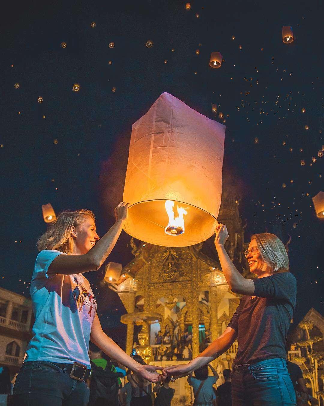 Twee damens die een brandende wensballon vasthouden