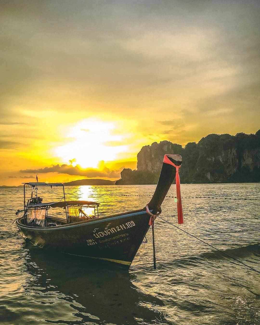 longtailboot met zonsondergang op railay west
