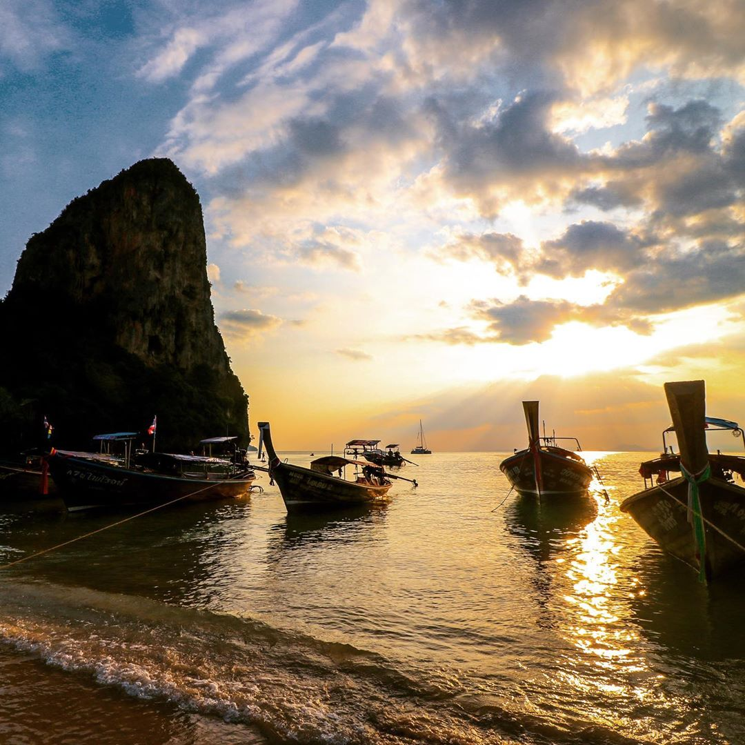 zonsondergang op phra nang beach met allemaal longtailbootjes op de voorgrond en de bekende rots op de achtegrond
