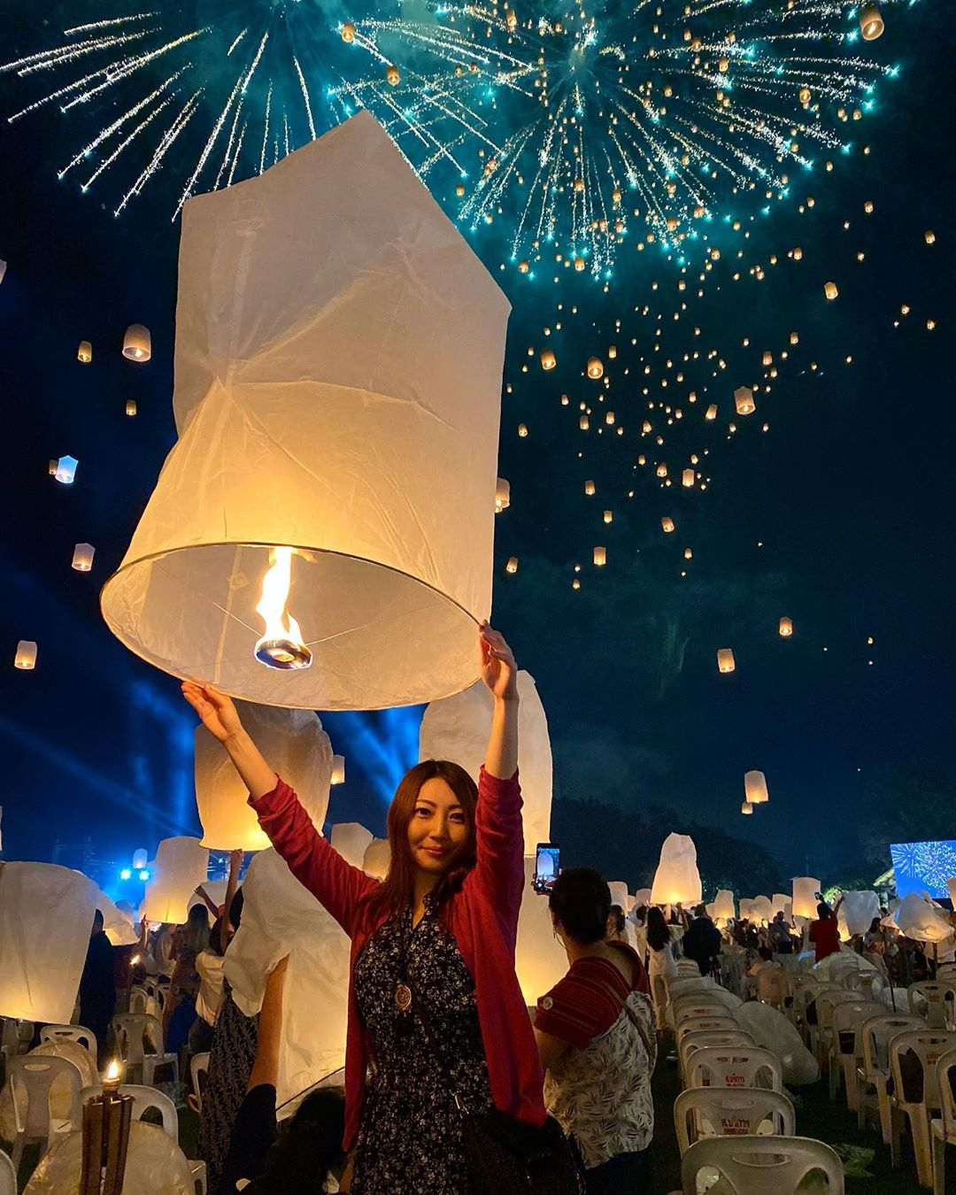 Thaise dame die een brandende wensballon vasthoudt met vuurwerk op de achtergrond