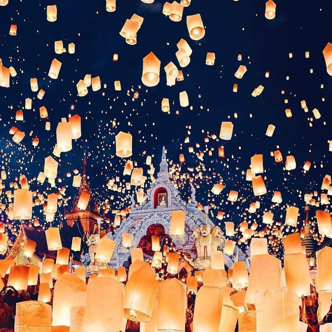 Brandende lampionnen in handen en in de lucht met een tempel op de achtegrond tijdens het Yee Peng Festival 2019