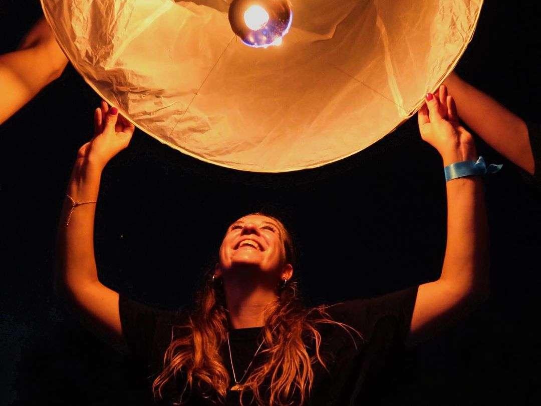 Gelukkig meisje die haar brandende lampion loslaat tijdens Yee Peng Festival 2019