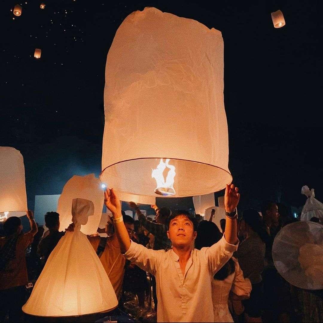 Jongen die een grote brandende lampion vastheeft