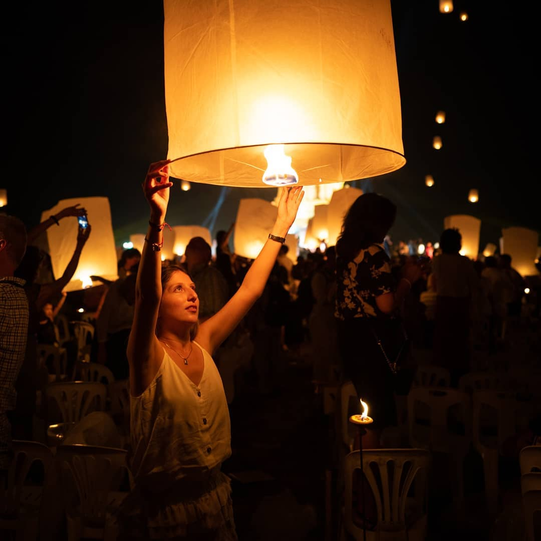 Meisje die een brandende wensballon vasthoudt tijdens het Yee Peng Festival 2019
