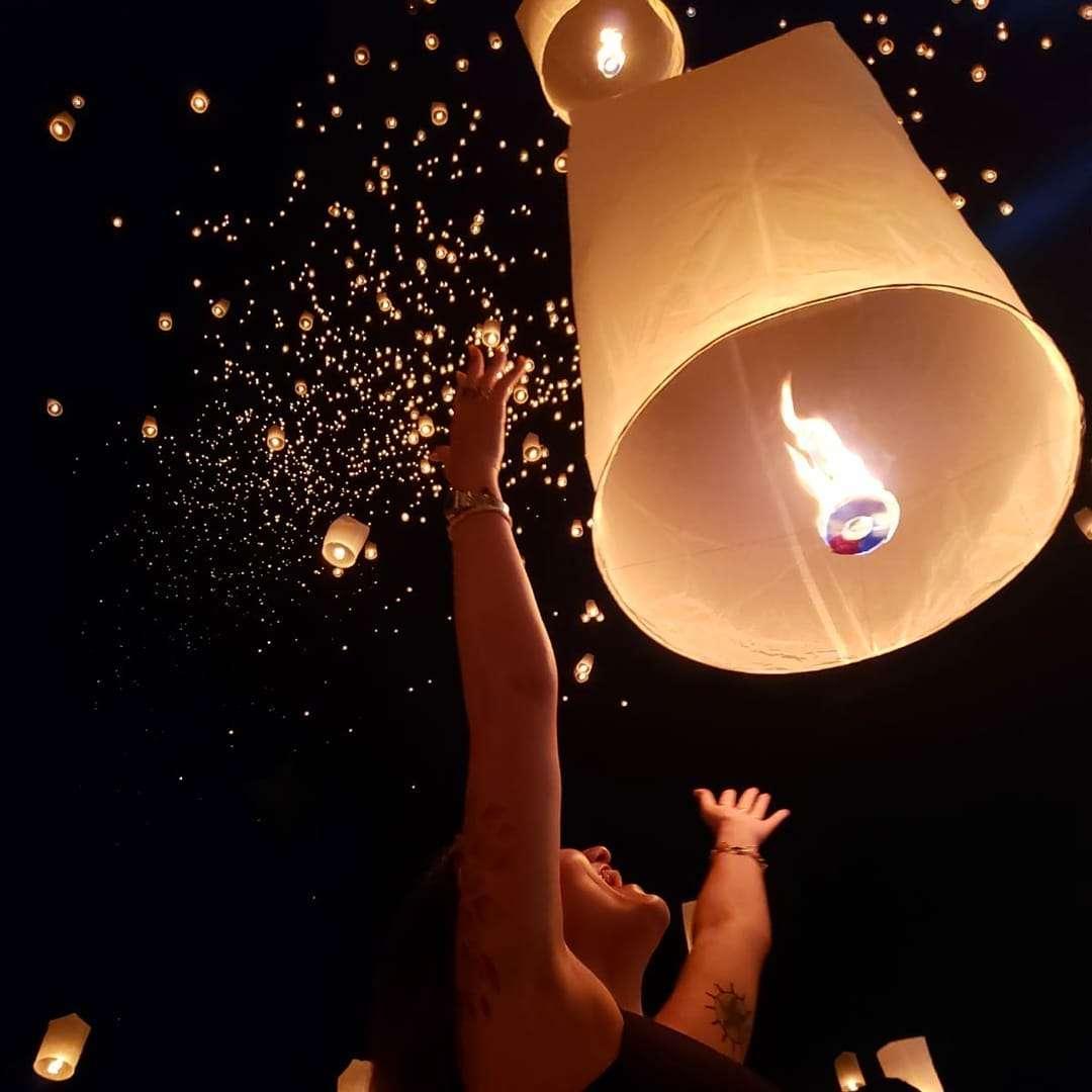 Meisje die haar brandende lampion loslaat tijdens het Yee Peng Festival 2019