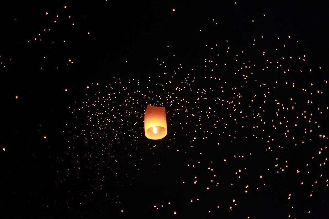 brandende wensballon met duizenden op de achtergond in de verte