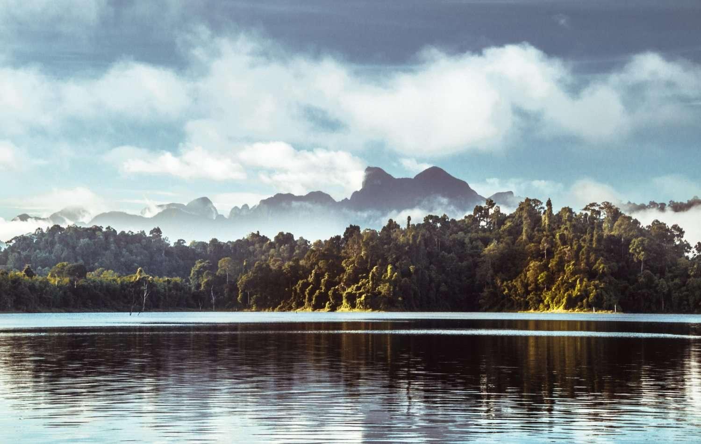 Het Cheowl Lan Lake met de bergen op de achtergrond gehild in wolken