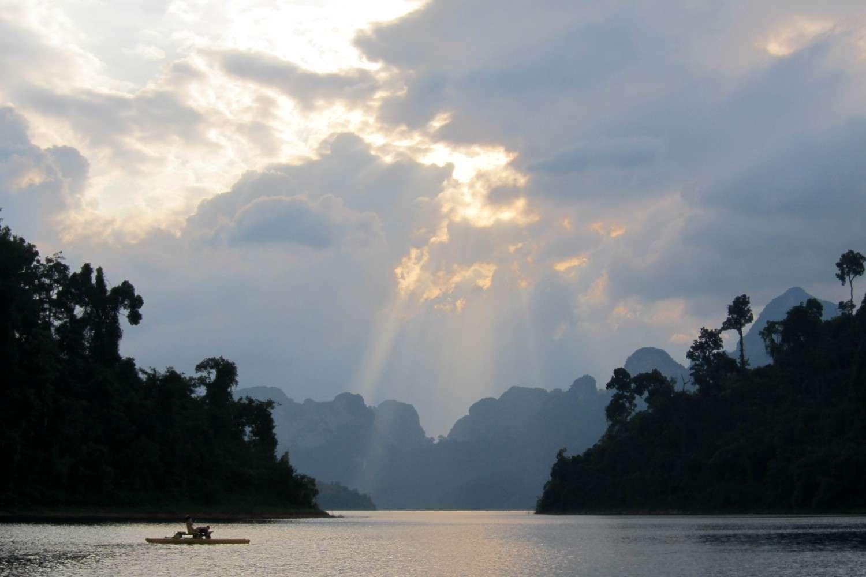 Zonnestralen die uit het wolkendek komen boven het Cheow Lan Lake