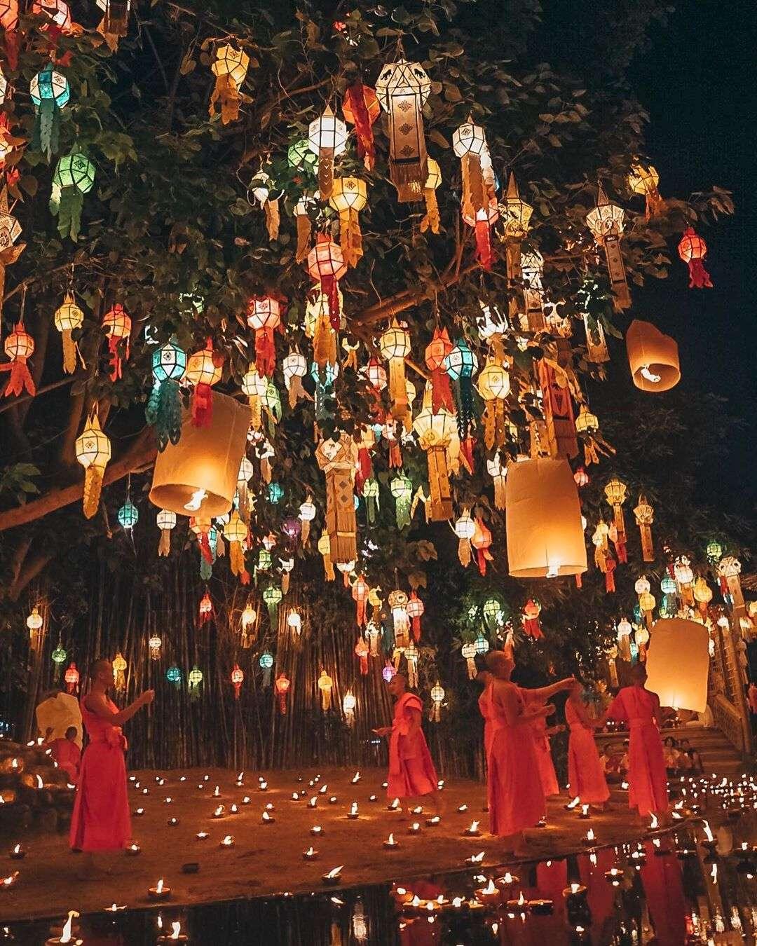 Boedistische monnikken onder een boom met lampionnen waarbij ze wensballonnen loslaten