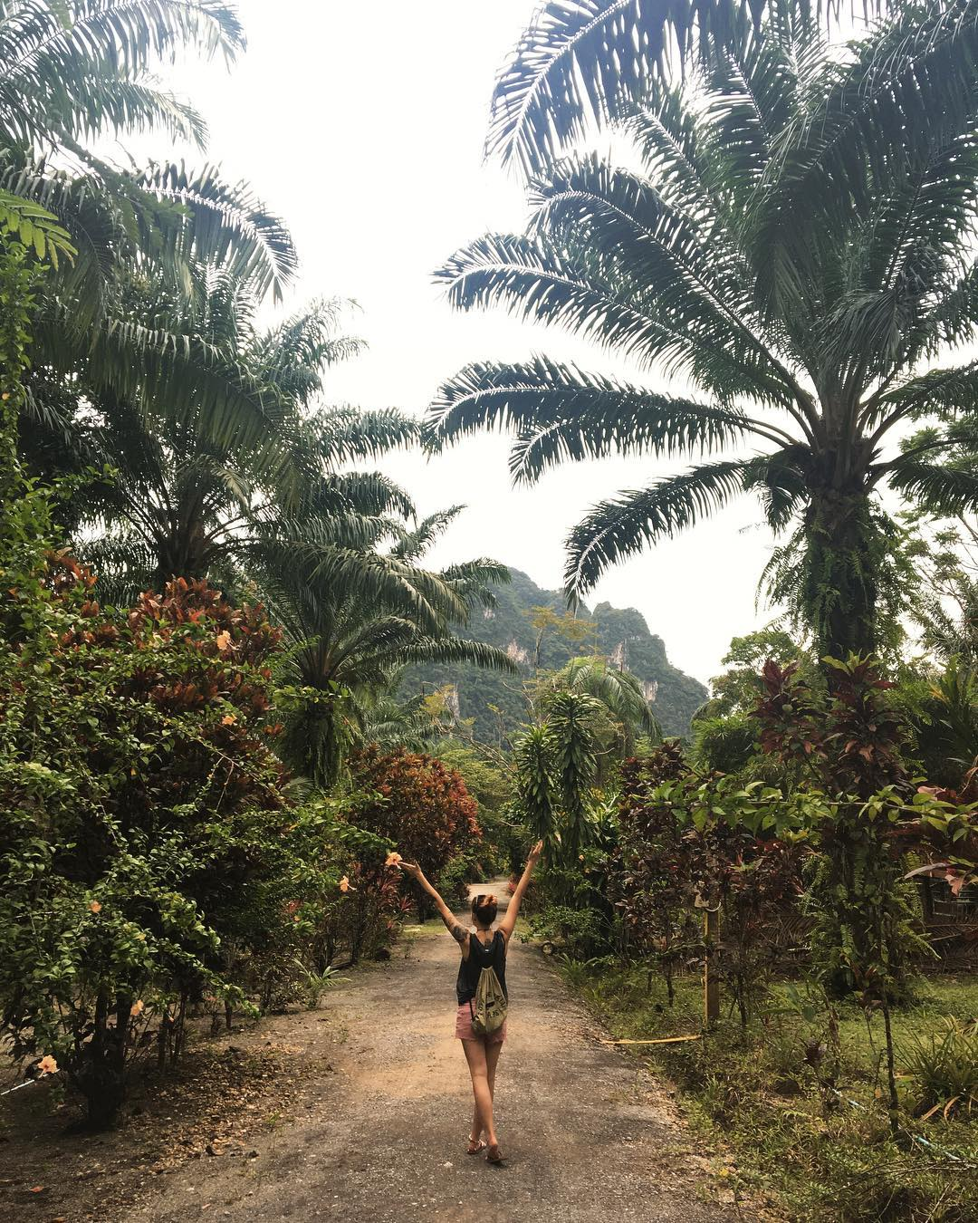 Girl happy with her arms up on a path in the jungle of Khao Sok National Park