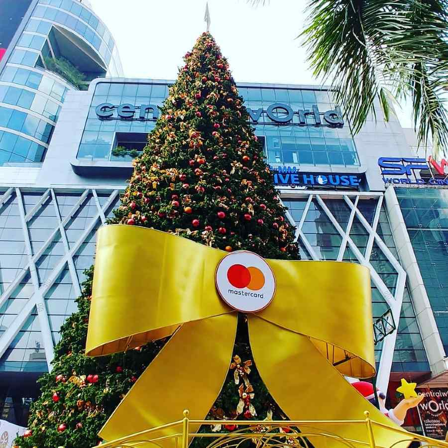 Large Christmas tree with yellow giant bow tie around it