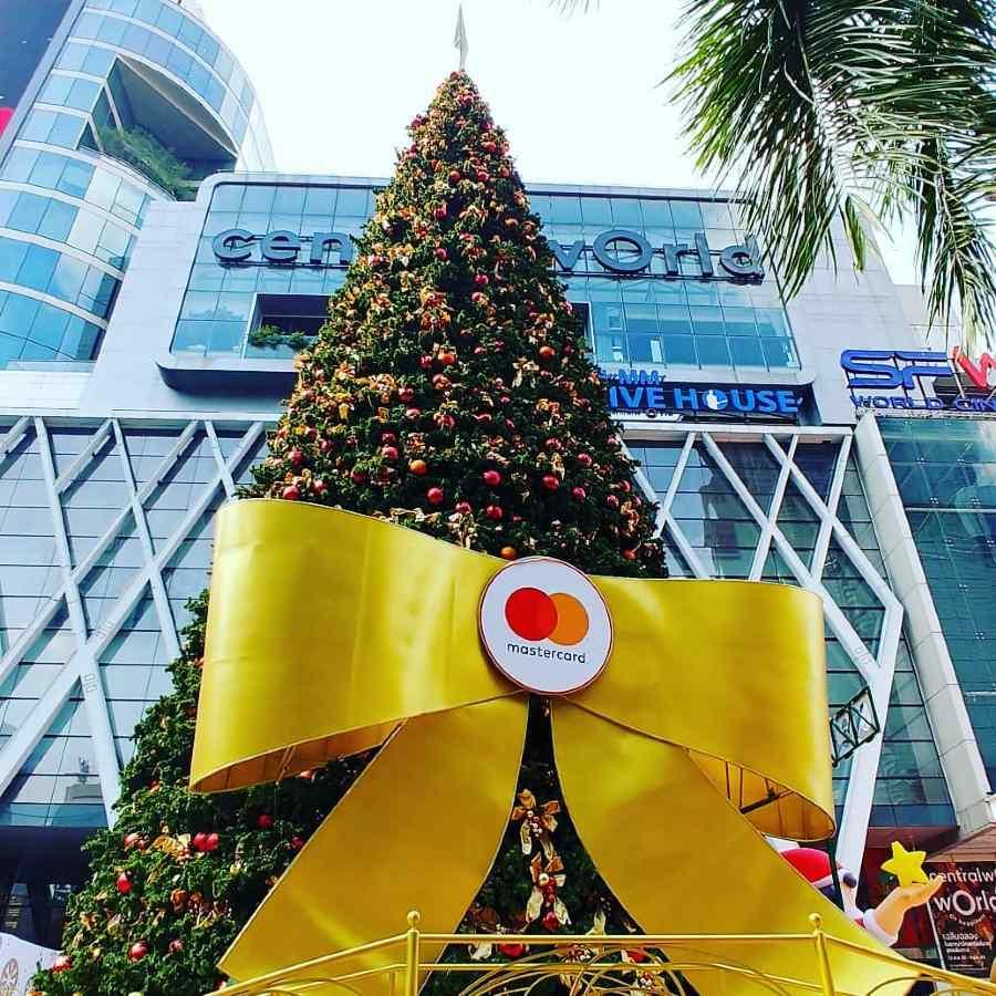 Grote kerstboom met gele reuze strik eromheen