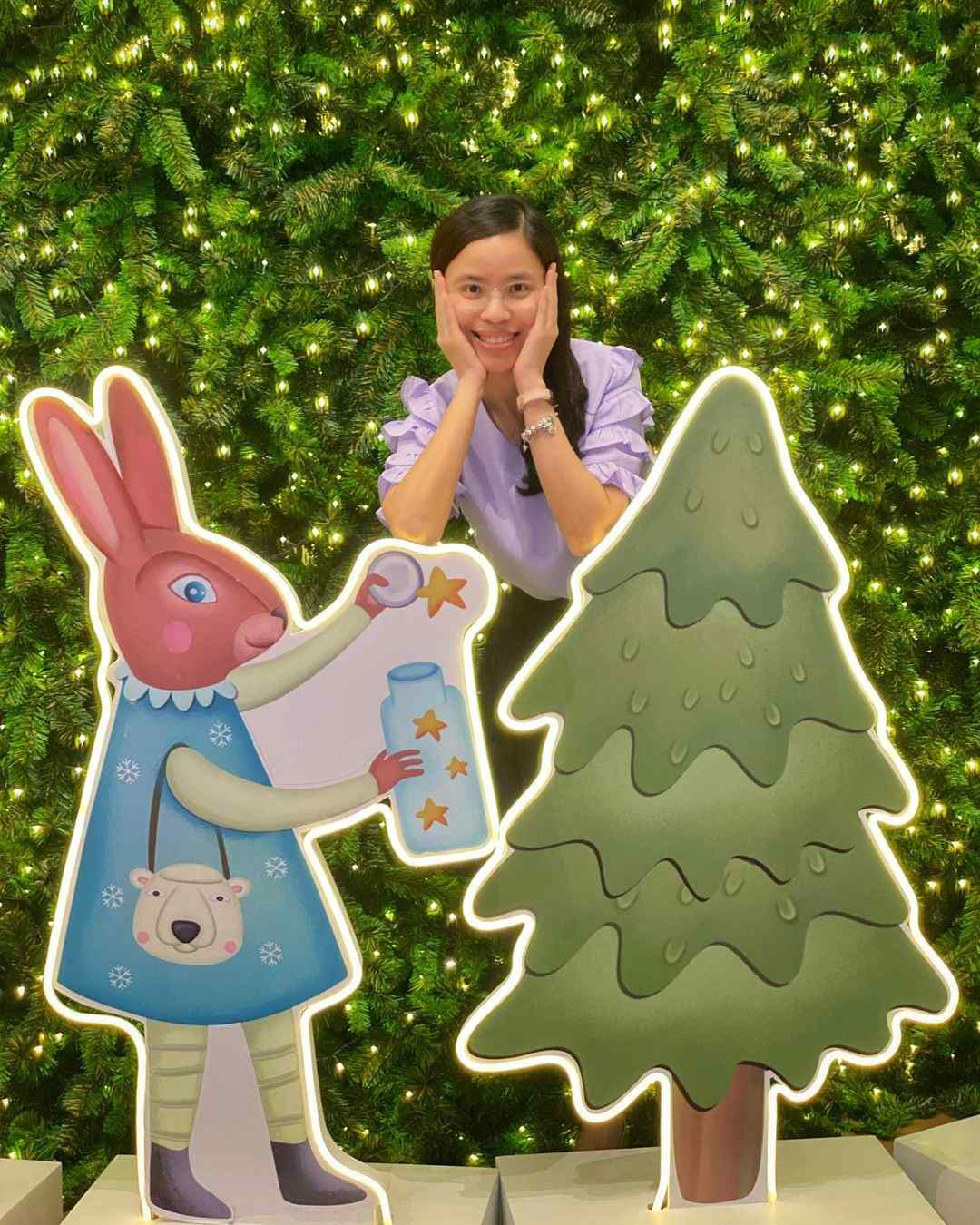 Rabbit decorating a Christmas tree with a star