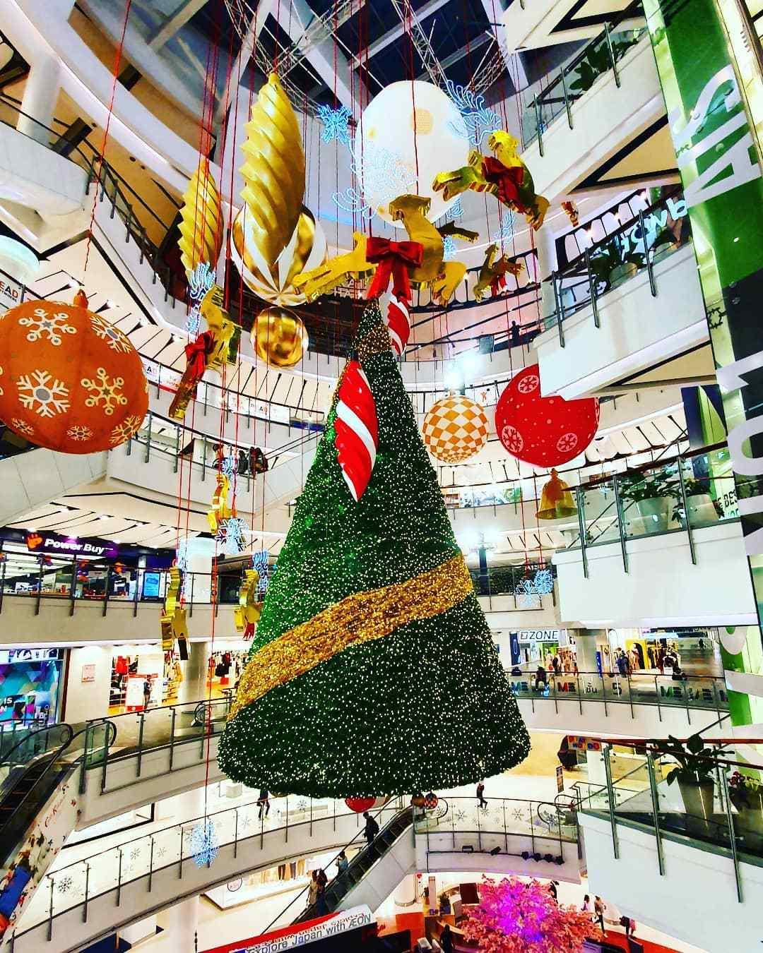 Hangende kerstboom in een winkelcentrum met versiering die ook hangt