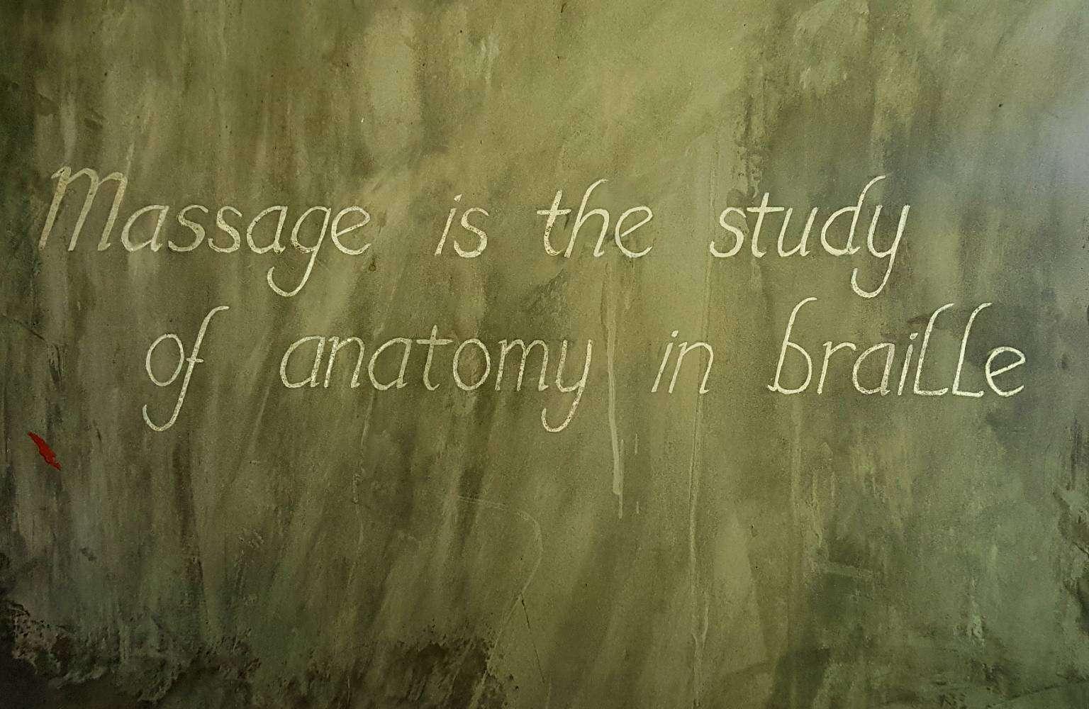 Krijtbord met tekst in de hut van Dr. Saad_ Massage is the study of anatomy in braille