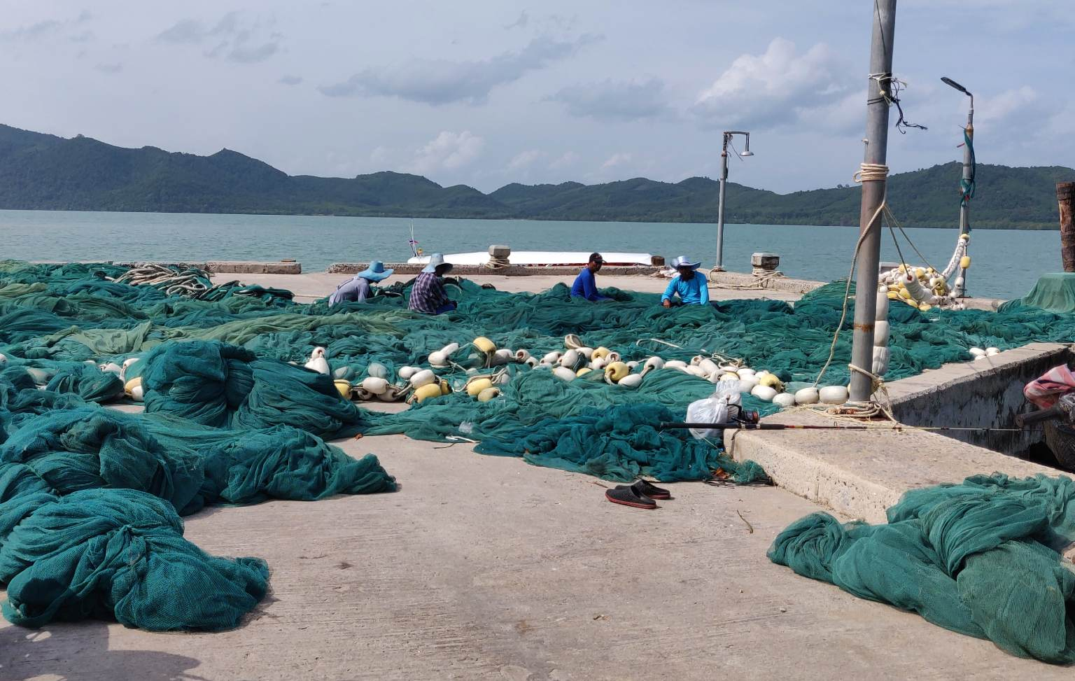 Koh Yao Yai Locals repair fishing nets on the pier