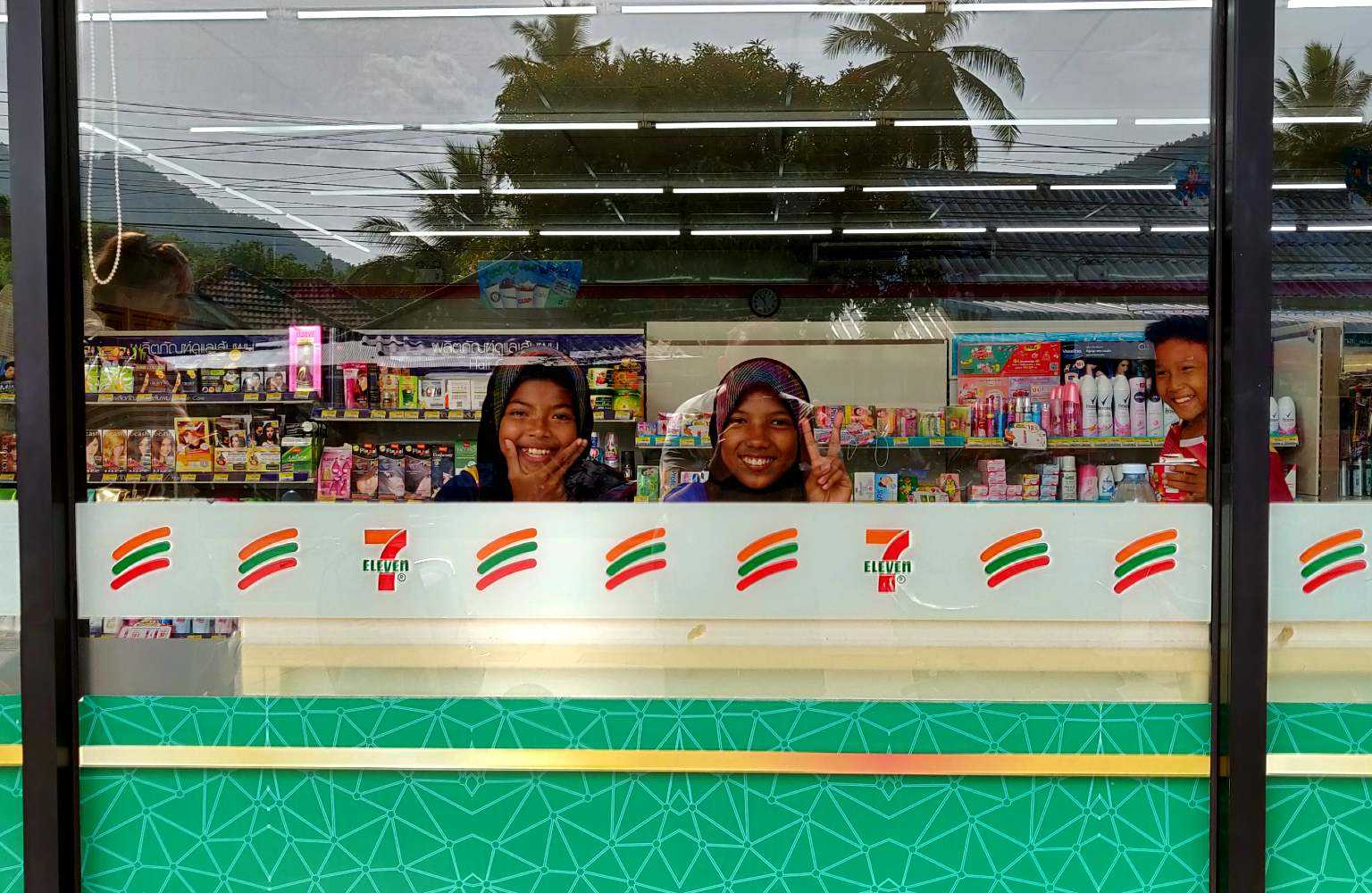 Smiling locals behind the glass of a local 7-Eleven on Koh Yao Yai