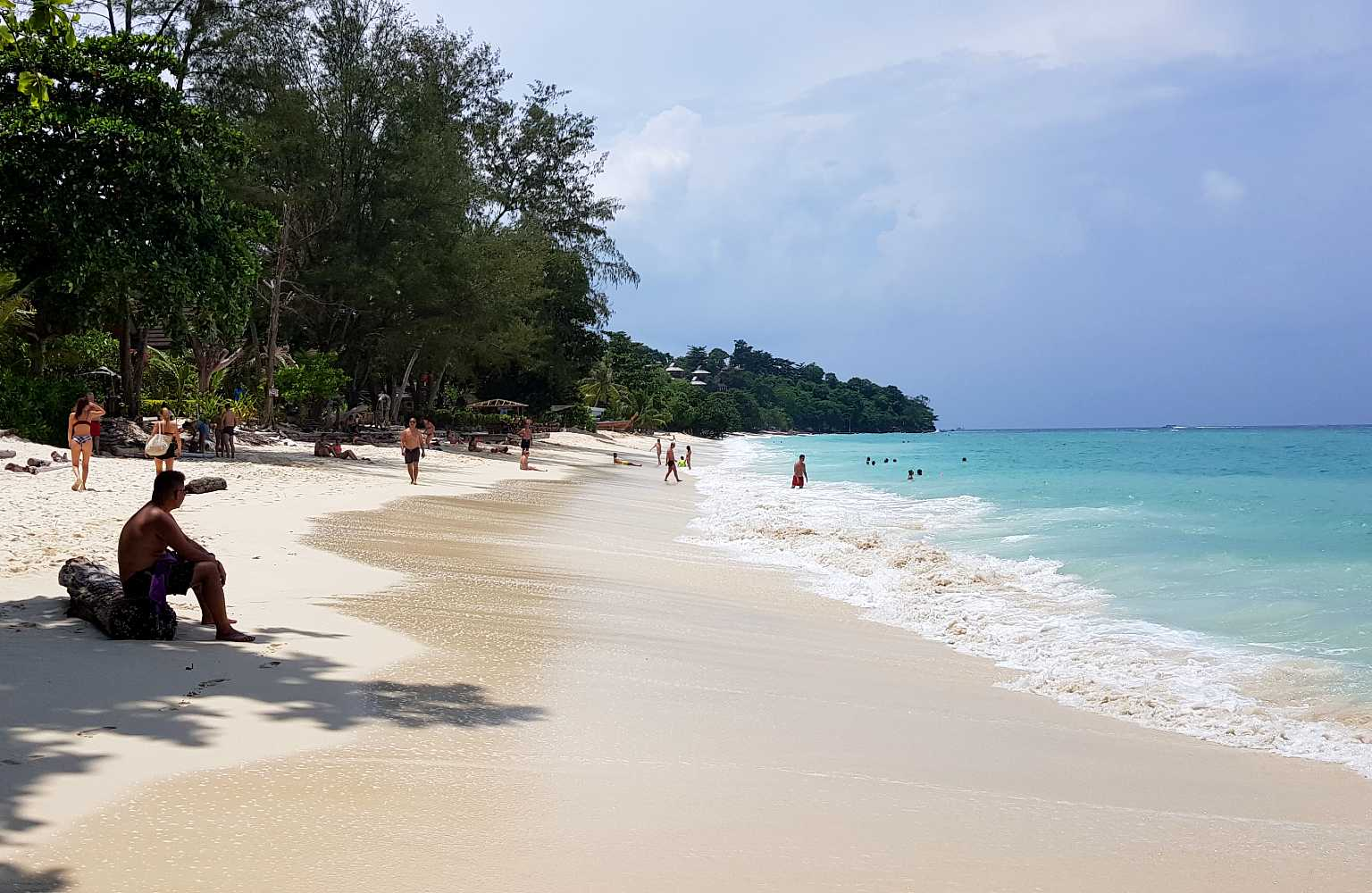 Long Beach, people sit on the white beach and swim in the blue sea on Koh Phi Phi