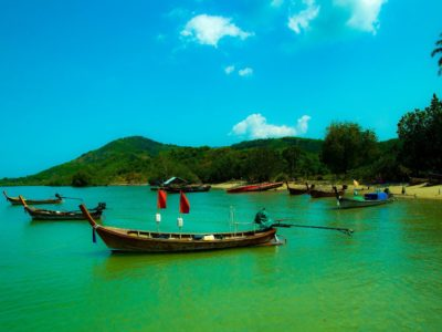 The Island Of Koh Yao Yai With Longtail Boats In Front Of It