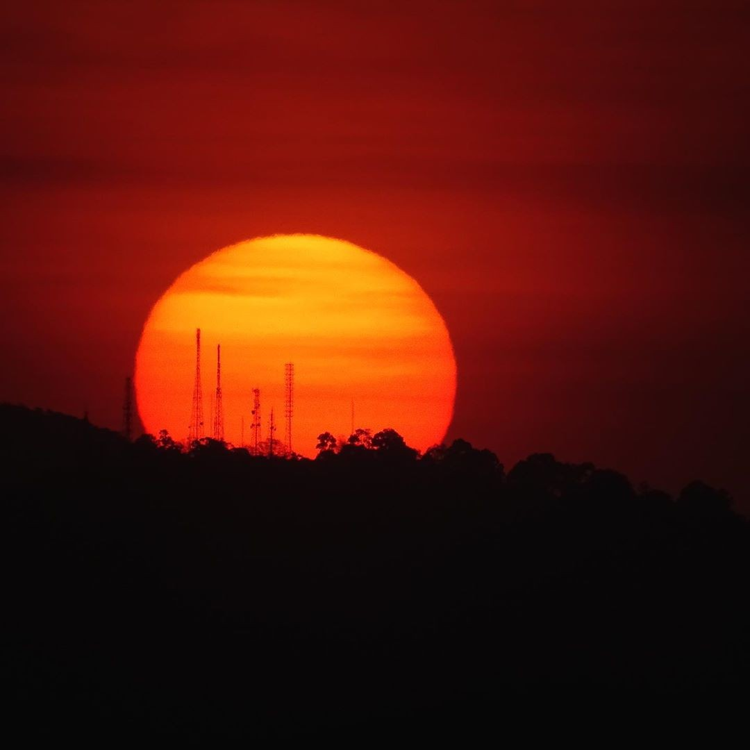 Very big red sun setting behind a mountain