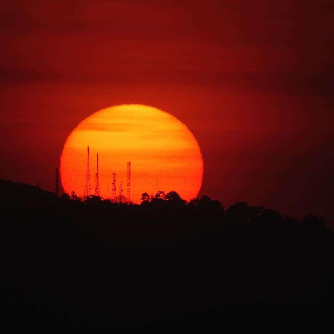 Hele grote rode zon die ondergaat achter een berg