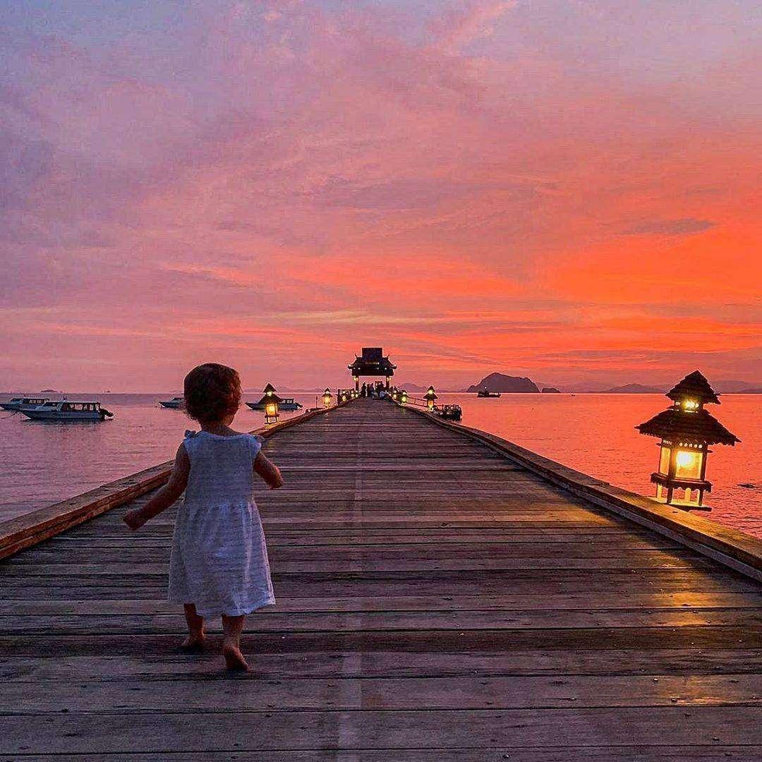 Jetinn Teppan Pier met een klein meisje erop tijdens zonsondergang