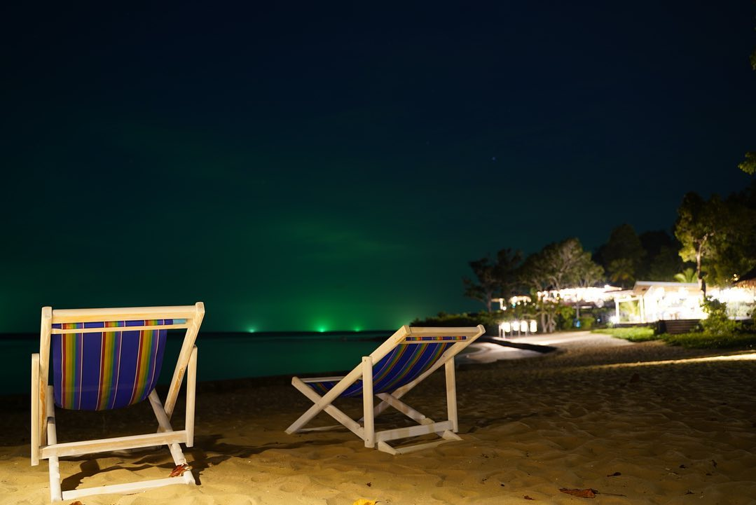 Fishing boats with their green light on in the distance as seen from Koh Yao Yai