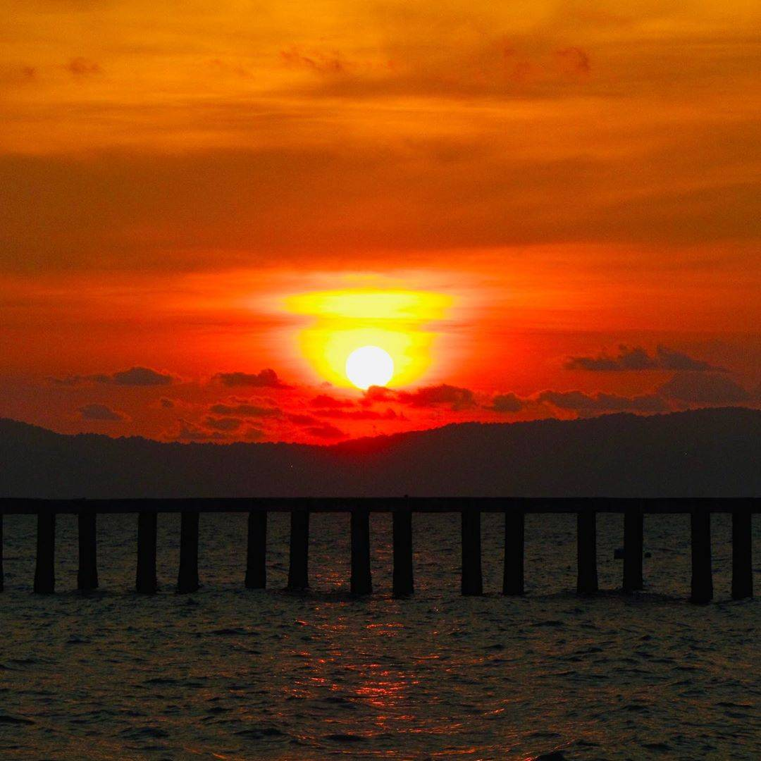 Sun setting with a pier in the foreground