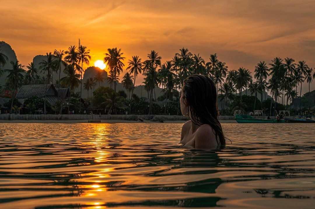 Meisje in de zee tijdens zonsondergang op Koh Phi Phi