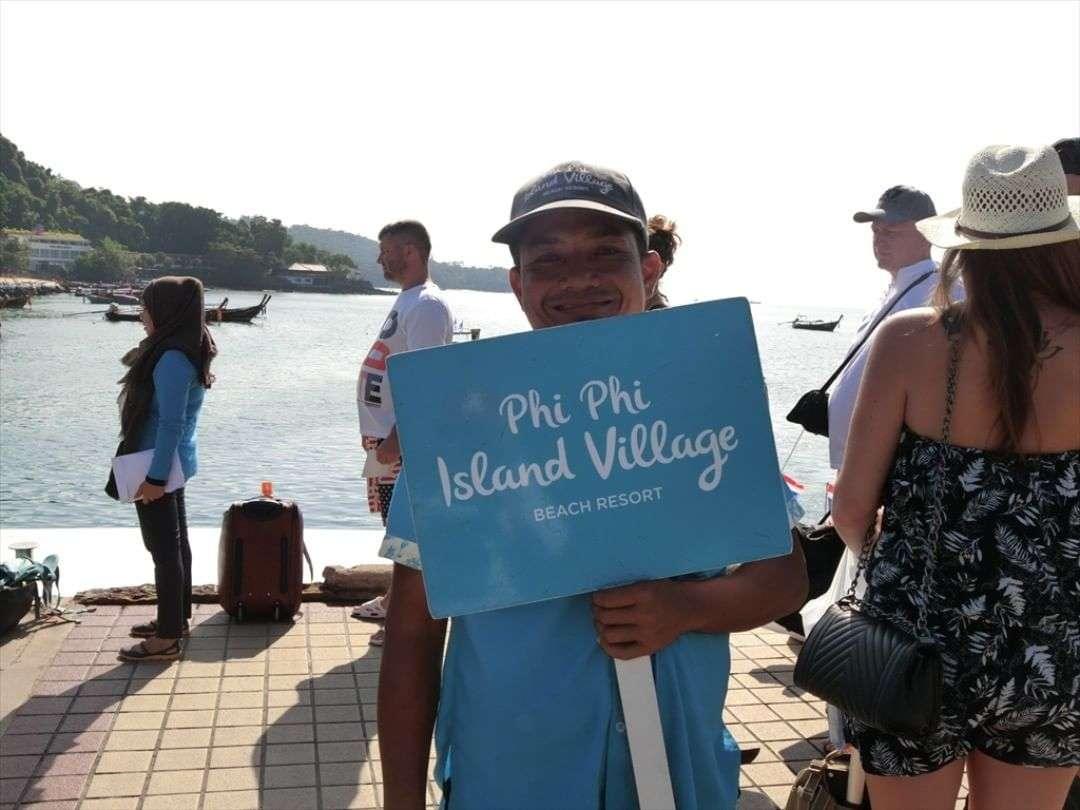Hotelpersoneel met bordje met daarop Phi Phi Island Village op de pier van Ton Sai, Koh Phi Phi