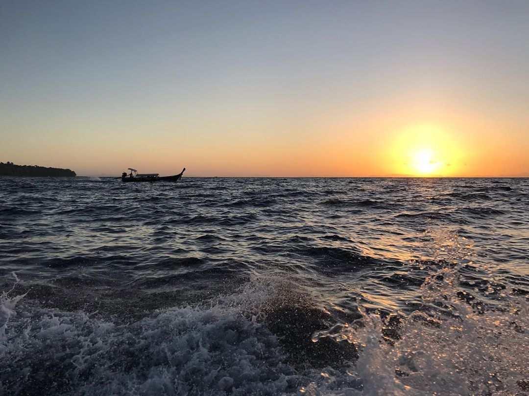 De zon onder zien gaan met de zee op de voorgrond op Koh Phi Phi Thailand