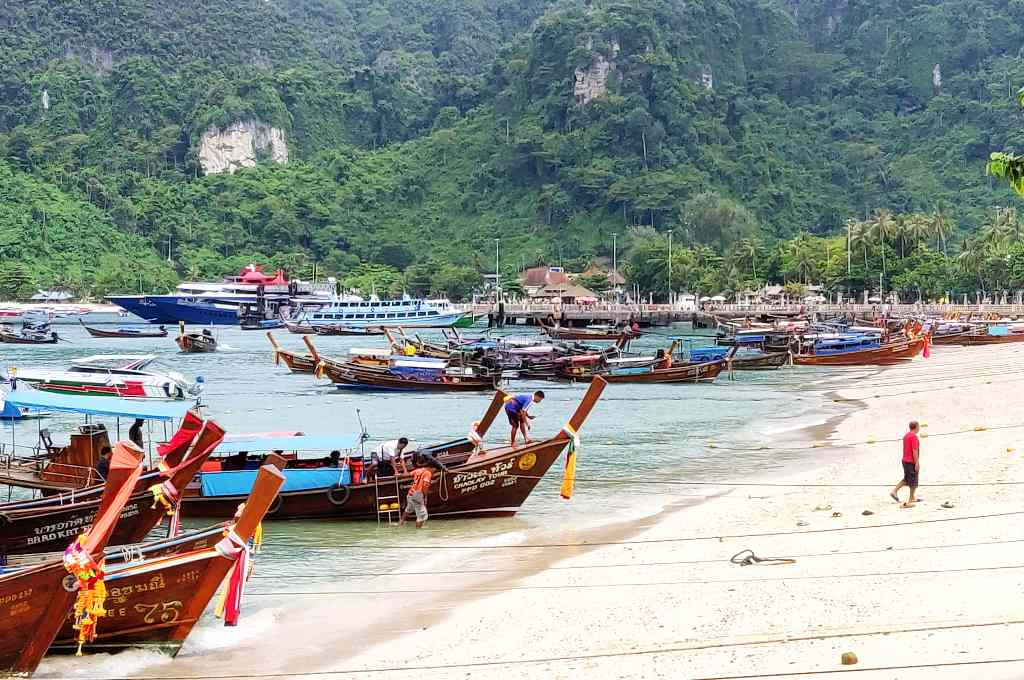 Ton Sai Beach with longtail boats and in the distance the Ton Sai Pier on Koh Phi Phi, Thailand.